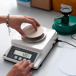 Midiendo el gramaje de un cartón con la balanza de precisión serie PCE-DMS