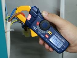 Amperímetro PCE-D3 sin contacto, detectando con luz señalizadora la tensión del cable de una instalación eléctrica.