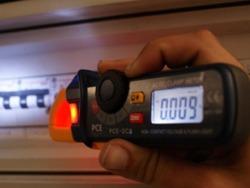 Amperímetro PCE-DC3 sin contacto, detectando el voltaje de un cuadro eléctrico en condiciones de baja luminosidad.