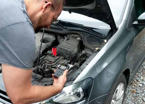 Verificando la batería de un coche con el comprobador de baterías de coche
