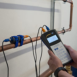 El medidor de caudal para líquidos por ultrasonido efectuando una medición en una tubería