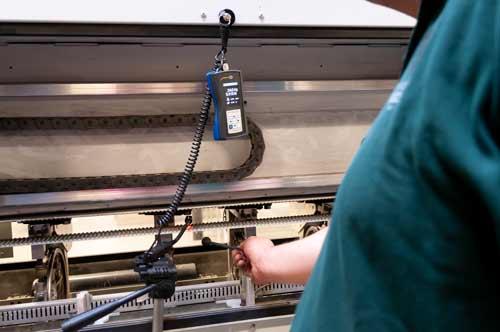 El medidor de tensión de correas en una máquina