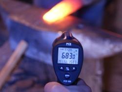 Pirómetro infrarrojo realizando una medición en un yunque.