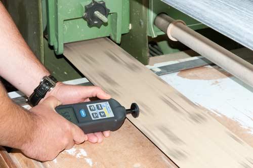 El tacómetro y estroboscopio PCE-T 260 midiendo la velocidad por contacto en una lijadora de cinta